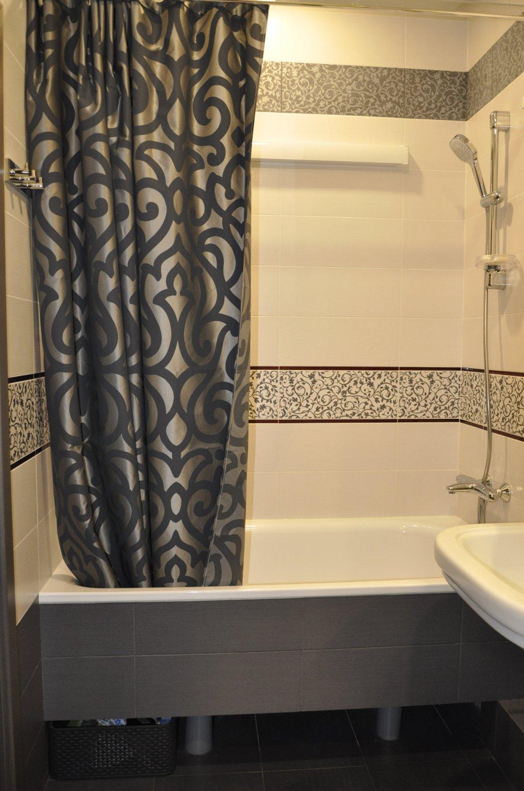Закрытая тёмной плиткой на гипсокартоне ванна в интерьере. Вид А