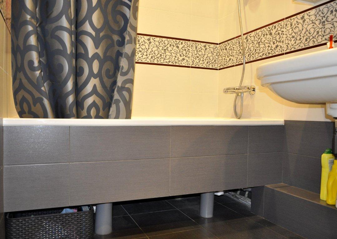 Закрытая тёмной плиткой на гипсокартоне ванна в интерьере