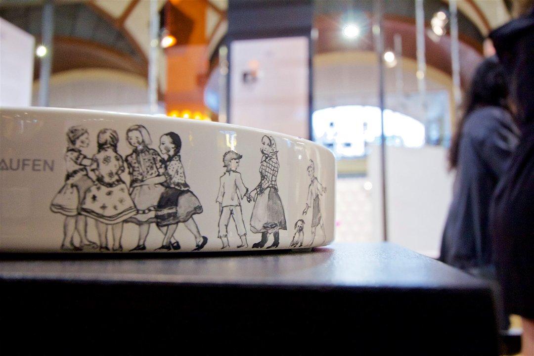 Иллюстрация к статье о современной тенденции продвижения санкерамики путём сотрудничества с художниками и росписи раковин. Художник Сьюзан Осако с участием детей во время росписи раковин на выставке, организованной специалистами Laufen в Праге